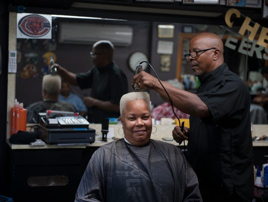 Cortez Bryant cuts the hair of Lynette Jackson at Bryant's