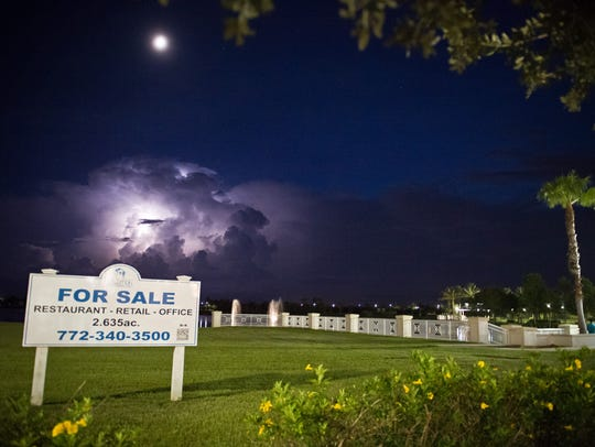 A sign advertising property for sale in Tradition is seen from Southwest Meeting Street, overlooking Lake Tradition and a distant storm.