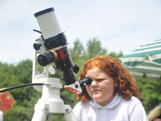 Isabella Sefcek, 7, of Plymouth, uses a solar telescope