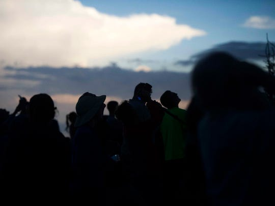 People look out at the view from Clingman's Dome parking area during a total solar eclipse in Great Smoky Mountains National Park Tuesday, Aug. 21, 2017.