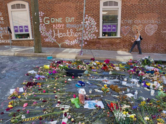 A woman walks through the memorial Friday, Aug. 18, 2017, at the site where Heather Heyer was killed in Charlottesville, Va. Heyer was struck by a car while protesting a white nationalist rally Saturday, Aug.12.