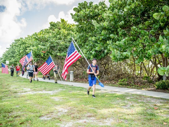 Rucking is a military term for hiking with weight on your back. two to three times a week. Pictured, members take part in a flag display.