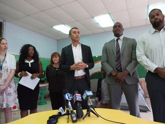 Camden City School District Superintendent Paymon Rouhanifard, center, announces that suspensions are down in Camden schools during a press conference at Yorkship Family School.
