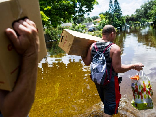 Jose Antonio and Alex Buso, residents of Bonita Springs affected by flooding, carry aid provided by the American Red Cross back to Jose's home on August 30.