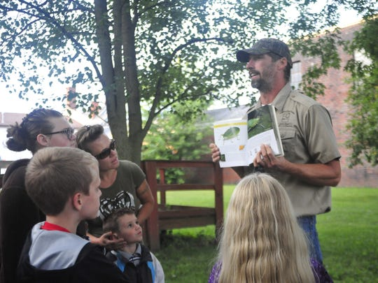 Josh Dyer shows a picture of a katydid, similar to the one he said was high in the tree above Thursday evening.