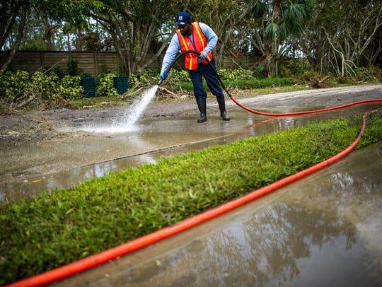 Darryl Jones, of St. Petersburg, sprays sewage from