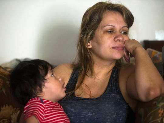 Lelin Romero holds her 1-year-old son, Ethan, as she listens to her boyfriend, Allan Rivera, talk about their financial situation Sept. 20, 2017, at their family's home in downtown Gatlinburg. They are survivors of last November's wildfires.