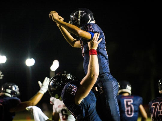 Estero High School quarterback Tanner Elliott is lifted by his team to celebrate their first touchdown against South Fort Myers High School on Friday, September 22, 2017