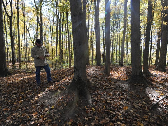 Dale Ferbrache, former Fairfield Union High School principal, walks toward an Adena mound at least 2,000 years old. The mound is located on the school district's land lab behind the high school and middle school.