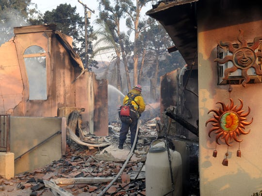 A firefighter sprays down a smoldering home in a Ventura hillside neighborhood on Tuesday as the Thomas Fire burned nearly 50,000 acres between Santa Paula and Ventura.