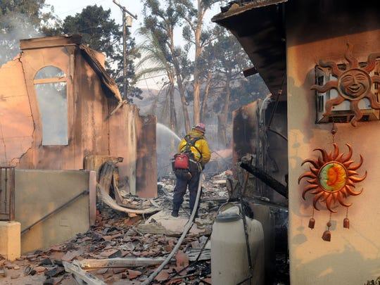 A firefighter sprays down a smoldering home in a Ventura hillside neighborhood Dec. 5.
