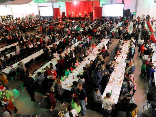 Diners eat and listen to music during the Feast of Sharing Tuesday at the Abilene Convention Center. Folks queued up for the free holiday meal, with the line snaking through the convention center lobby, then outside and into the north side courtyard.