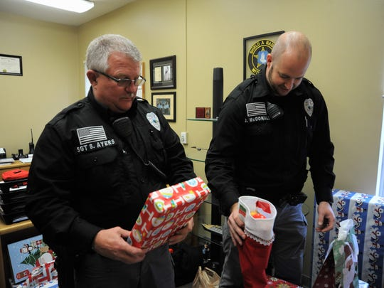 Sergeant Stacy Ayers, left, and officer John McDonald with the Black Mountain Police Department check out gifts purchased with funds raised by their department and the town's public services department.