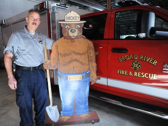 Rob White, a firefighter with the Broad River Volunteer Fire and Rescue Department, holds up a 6-foot metal likeness of Smokey Bear that was recently taken from its post nearby.