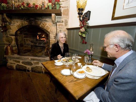 A couple enjoys a birthday dinner near the fireplace