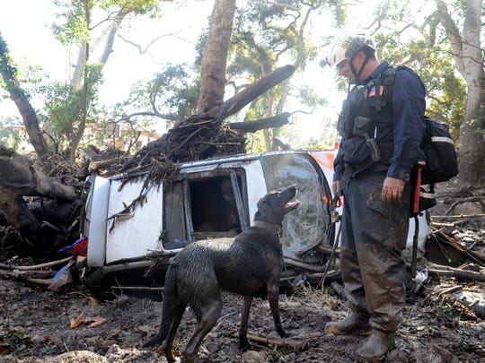 Brent Brainard and his dog Decker of California Task Force 8 of San Diego search for missing people Thursday on East Valley Road in Montecito.