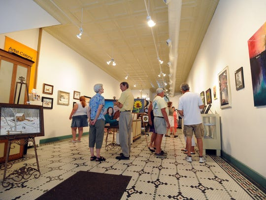 Visitors view the art on display at the Zanesville Appalachian Arts Project (ZAAP) Gallery in Zanesville during a First Friday event. ZAAP is part of the Artist Colony of Zanesville, which has helped revive the city's downtown district in the decade since the Great Recession.