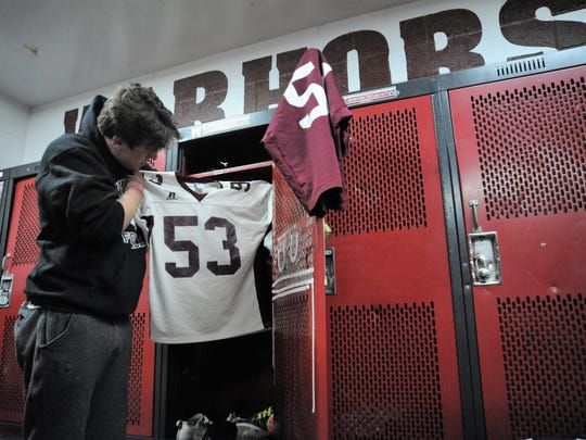 Kaleb Woods, a senior who played on the Owen High School varsity team for three seasons, takes one last look at his number 53 before putting it away for good.