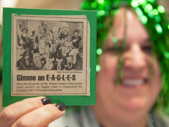 Assistant Principal Kristen Speakman displays a photograph of a Super Bowl Eagles pep rally from 2005 that ran in The Daily Journal, as Speakman takes part in a Super Bowl Eagles pep rally held at Dr. WilliamMennies Elementary Schoolin Vineland on Friday.