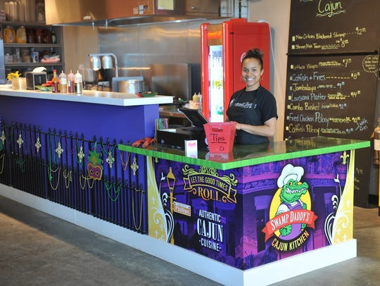 Inkka Beaudion, owner of Swamp Daddy's Cajun Kitchen, poses behind the counter of her new restaurant downtown at Jones 421.