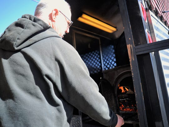 Buddy Clemons stokes the fire on the grill in the Sqweelin' Pig BBQ food truck, which moves to Black Mountain on March 3.