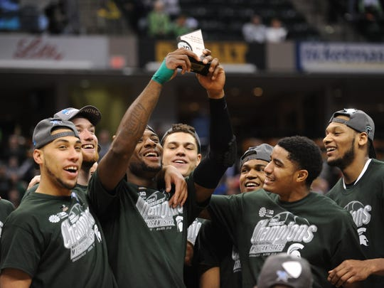 MSU's Branden Dawson celebrates winning the MVP with his teammates after defeating Michigan in the Big Ten Championship finals Sunday.