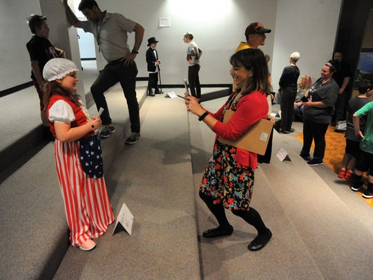 Jaime Goodwin takes a picture of a student dressed as Betsy Ross in the theater at Black Mountain Primary School during the class's March 28 wax museum presentation.