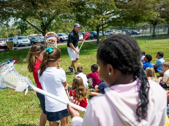 Marshall Huggins, the Collier County US Lacrosse volunteer, instructs children at Vineyards Elementary School on Thursday, March 29, 2018.