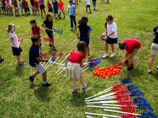 Vineyards Elementary School students choose donated lacrosse equipment to play with during PE class on Thursday, March 29, 2018.