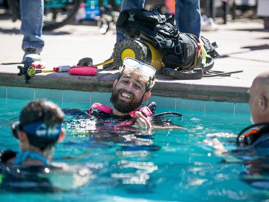Veteran Marc Laspes laughs in a pool while scuba diving