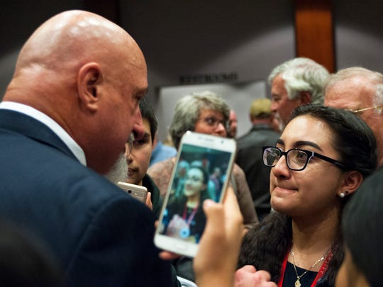Kimberly Casas, right, confronts Henderson County Sheriff Charles McDonald after a candidate debate Tuesday. A friend of Casas holds a phone in the air to record the interaction.