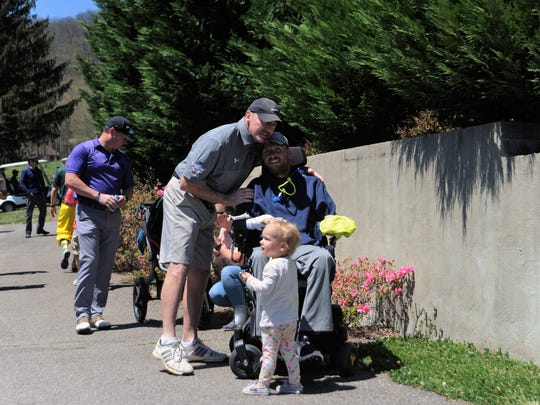 Kenny Ford embraces Britten Olinger at the Britten Strong Golf Tournament at the Black Mountain Golf Course in 2018. The fundraiser for the Montreat College track and field coach returns for its second year on Oct. 11.