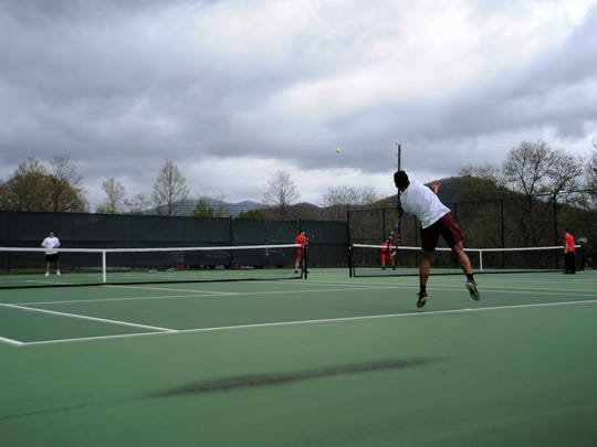 Junior Lorenz Hoover elevates as he delivers a serve at home on April 25 in the Western Highlands  Conference tournament.