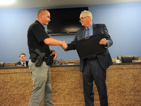 Sergeant Chris Staton is presented with a certificate recognizing his life-saving actions in March by mayor Don Collins on May 14.