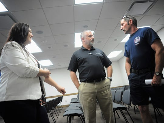 Public services director Jamey Matthews, center, checks in with Black Mountain Fire Department battalion chief Jimmy Bingham while town clerk Angela Reece looks on.