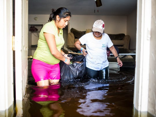 Nayeli Vasquez, left, and her aunt, Basilica Ventura, right, carry the last salvageable valuables out of their flooded home on Quinn Street after Hurricane Irma in Bonita Springs on Sept. 12, 2017.