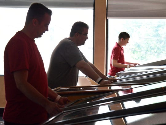 Pinball players rack up points at the arcade on a recent