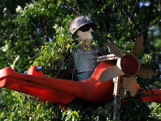 A combination of junk pieces made by Ernest Johnson sits above his fence May 30, nearly enveloped by a creeping vine.