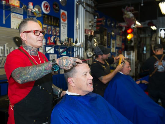 Joe da Barber discusses a hair cut in progress at Barbers