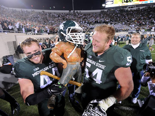 MSU's Marcus Rush and Connor Kruse hold up the Paul