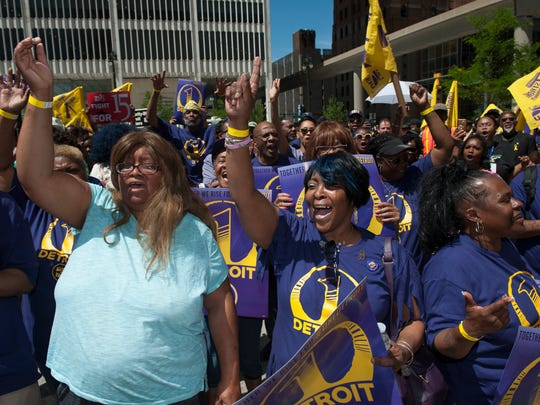 Kimberly Walker, left, and Wanda Hudson, center, both of Detroit, chant along with fellow SEIU Union members during a rally for higher wages and the One Detroit campaign. Hudson has worked as a custodian for 26 years and only makes $12.12 per hour, she said.