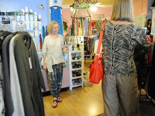 Connie Pruitt, manager of Periwinkles on Cherry Street, helps customers in the store, which participated in Dine & Shop Day on June 16.