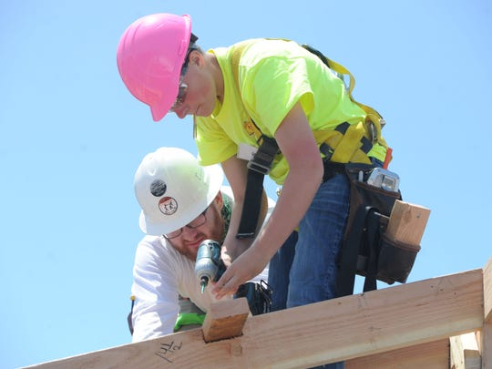 Kat Meadors, front, and lead instructor Daniel Bell work on setting the rafters on a tiny house. Middle and high school girls are working this week on a construction project as part of a day camp at the Ventura County Office of Education Career Education Center.