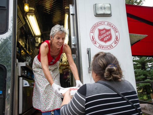 Sara Fisher hands out a meal from a Salvation Army