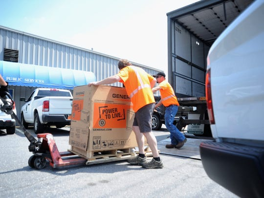 Town employees unload a tractor-trailer in the full