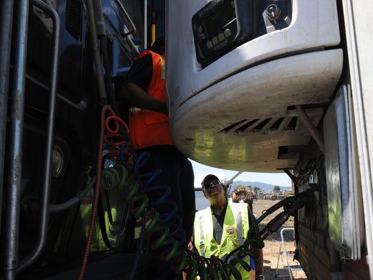En esta foto de archivo, Shailendra Pratab, supervisora de campo de la Junta de Recursos del Aire estatal, mira mientras un conductor de camión abre la unidad de refrigeración de su remolque para una inspección en un punto de revisión en el sur de Salinas. Se calcula que los conductores de camiones ganan un salario promedio anual de $47,482.