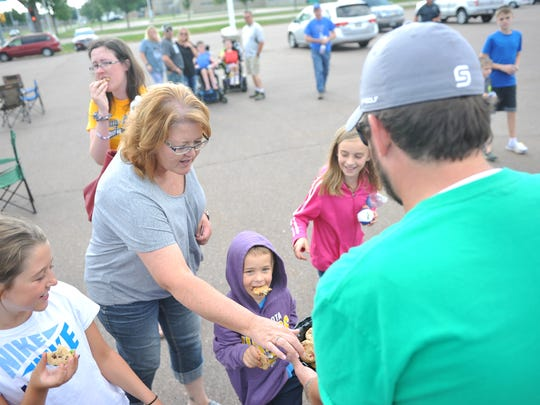 Families snatch up cookies at a tailgate before the Sioux Falls Canaries game Saturday. The families were there as part of a Rebekah's Legacy Foundation event for kids with life-altering illnesses.