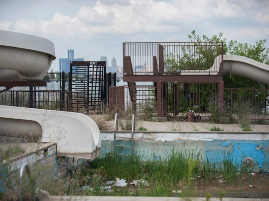 Grass grows in the dirt at the bottom of the empty pool for the dormant waterslide on Belle Isle.
