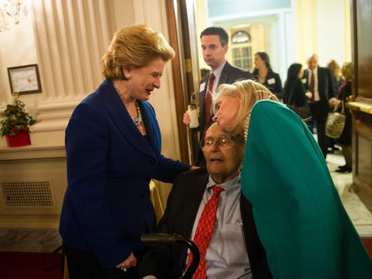 Retiring Congressman John Dingell gets a hug from his wife Debbie Dingell, right, while greeting Michigan Senator Debbie Stabenow, left, at a reception on Capitol Hill on Dec. 10, 2014.