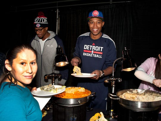Pistons forward Caron Butler serves macaroni and cheese during a Thanksgiving dinner for 700 people from Wayne and Oakland counties Tuesday at the Palace. Pistons forward Cartier Martin is pictured at left.